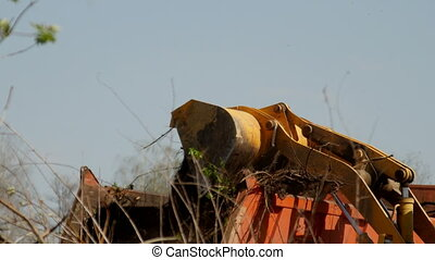 Wheel loader excavator clearing the territory for building a...