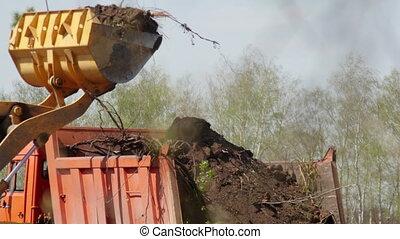 Wheel loader excavator loading construction garbage in a dump truck