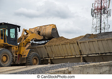Wheel loader Excavator unloading sand with water during...