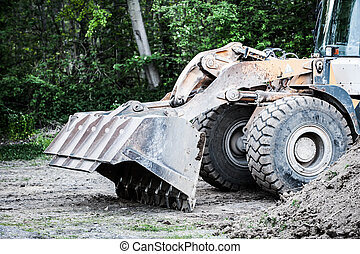 wheel loader stands at building site in front of forest