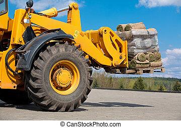 Wheel loader transportation pallet with green grass rolls