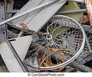 wheel of a bicycle in the container of scrap metal