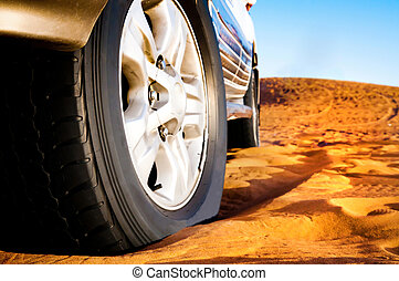 wheel of a car on the sand