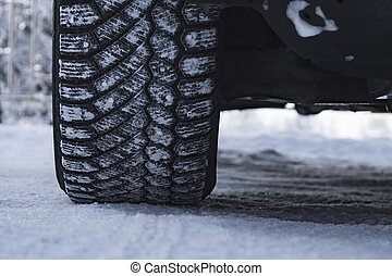 Wheel of car is coated in winter tires in snow. View from the front.