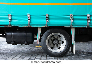 Wheel of large truck parked in city street. Freight...