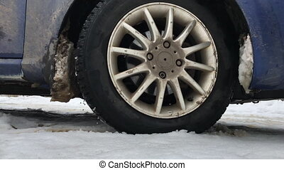 Wheel of the car slips and rides through the snow in the...