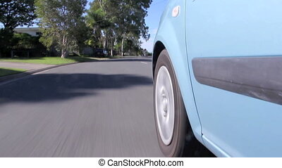 Low angle view of front car wheels travelling along a road and coming to a stop.