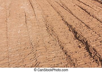 Wheel tracks on the soil as backhoe service