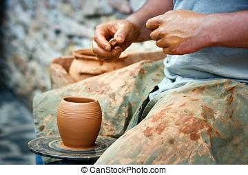 Wheel Wedging Clay. Medieval craftsman modelling a clay mug...