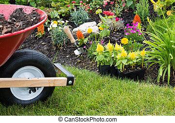 Wheelbarrow alongside a newly planted flowerbed with...