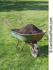 Wheelbarrow  full of compost on lawn