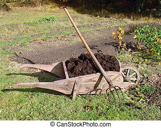 Old wooden wheelbarrow full of manure and pitchfork
