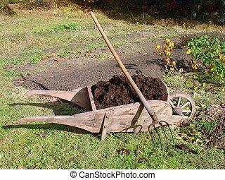 Wheelbarrow full of manure - Old wooden wheelbarrow full of...