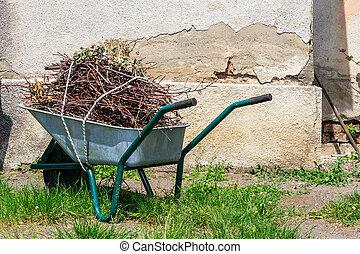 wheelbarrow near the old wall - wheelbarrow filled with cut...