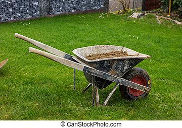 wheelbarrow with full of soil at green grass garden