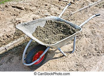 Wheelbarrow with mortar on road construction