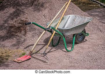 Wheelbarrow with shovel and rake