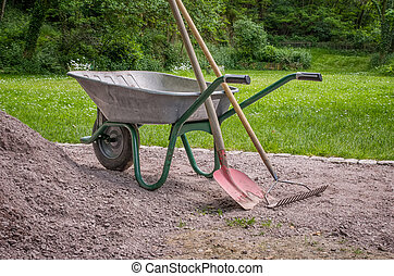 Wheelbarrow with shovel and rake