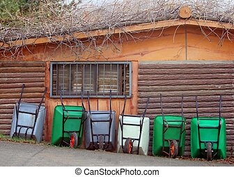 Wheelbarrows lined up against a shed