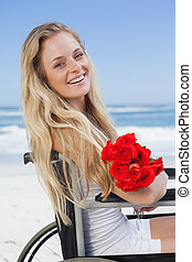 Wheelchair bound blonde smiling at the camera on the beach holdi