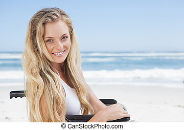 Wheelchair bound blonde smiling at the camera on the beach...