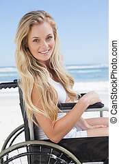Wheelchair bound blonde smiling at the camera on the beach ...