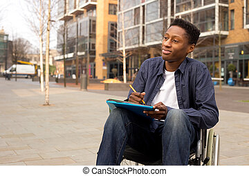 wheelchair bound man looking thoughtful with folders and a pen