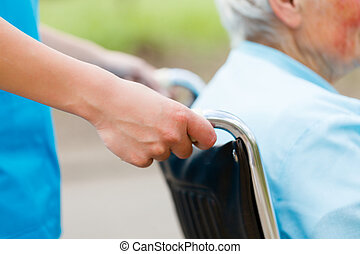 Wheelchair - Elderly woman in wheelchair pushed by nurse's...