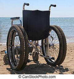 Wheelchair on the beach sand