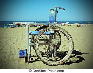 wheelchair on the sand beach near the sea