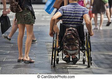 Wheelchair - Man strolls down the sidewalk with wheelchair