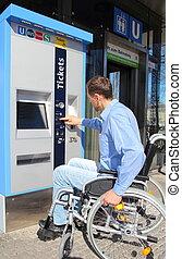 Wheelchair user on a ticket machine