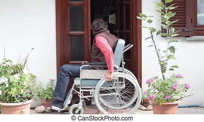 wheelchair - man in wheelchair goes out of his home
