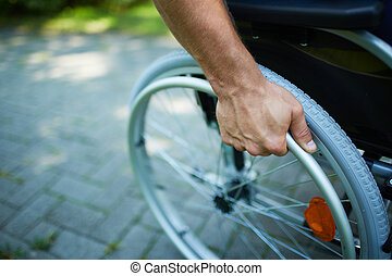 Wheelchair walk - Close-up of male hand on wheel of...