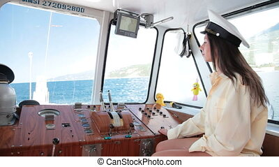 wheelhouse of ship - woman in uniform of captain in the...