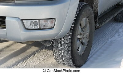 Wheels of a car traveling on winter