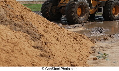 Wheels of a large yellow forklift ride through the mud,...