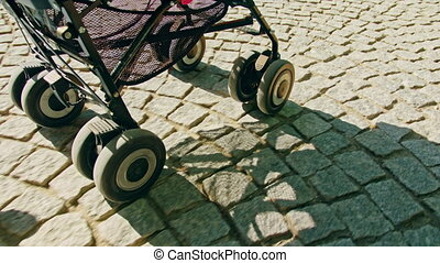 Wheels of a Stroller Rolling on Cobble Stone Road