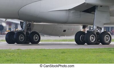 Wheels of airliner undercarriages. Landing gear of taxiing airplane