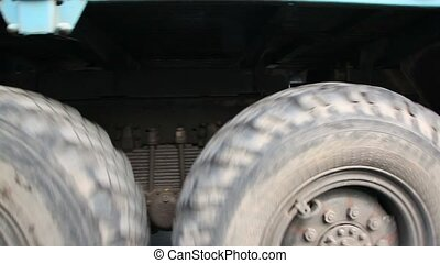 Wheels of big truck rotates, close-up view in motion
