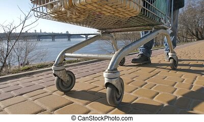 Wheels of cart with homeless man's belongings - Wheels of...