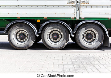 wheels of large truck and trailers at parking lot
