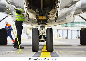 Wheels of the airplane - Airplane parked at the airport and...