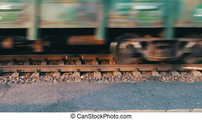 Wheels of the train moving along the rails closeup