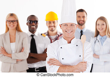 When I grow up I will be a chef. Confident male chef in uniform keeping arms crossed and smiling while group of people in different professions standing in the background