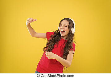 When the soul is singing. Adorable small child singing on yellow background. Cute little girl listening to music in earphones and singing song. Musician enjoying solo singing