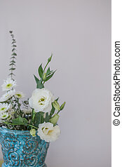 Whilte lisianthus in turquoise vase with copy space