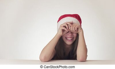 Whimsical hysterical girl teenager in a Santa Claus hat is...