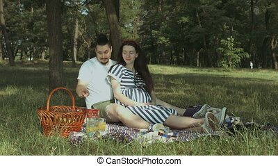 Whimsical pregnant woman choosing fruits on picnic