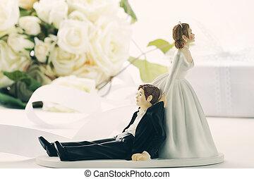 Closeup of whimsical wedding cake figurines on white